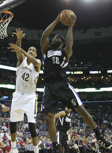 Mar 31, 2014; New Orleans, LA, USA; Sacramento Kings forward Reggie Evans (30) grabs the ball in front of New Orleans Pelicans center Alexis Ajinca (42) in the second half at the Smoothie King Center. Sacramento defeated New Orleans 102-97. Mandatory Credit: Crystal LoGiudice-USA TODAY Sports