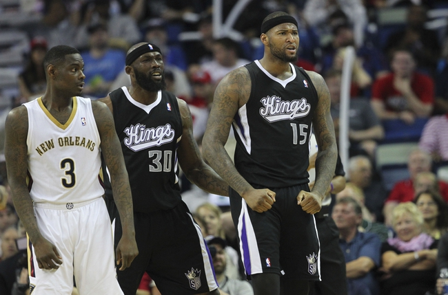 Mar 31, 2014; New Orleans, LA, USA; Sacramento Kings center DeMarcus Cousins (15) and forward Reggie Evans (30) celebrate a basket beside New Orleans Pelicans guard Anthony Morrow (3) in the second half against the New Orleans Pelicans at the Smoothie King Center. Sacramento defeated New Orleans 102-97. Mandatory Credit: Crystal LoGiudice-USA TODAY Sports