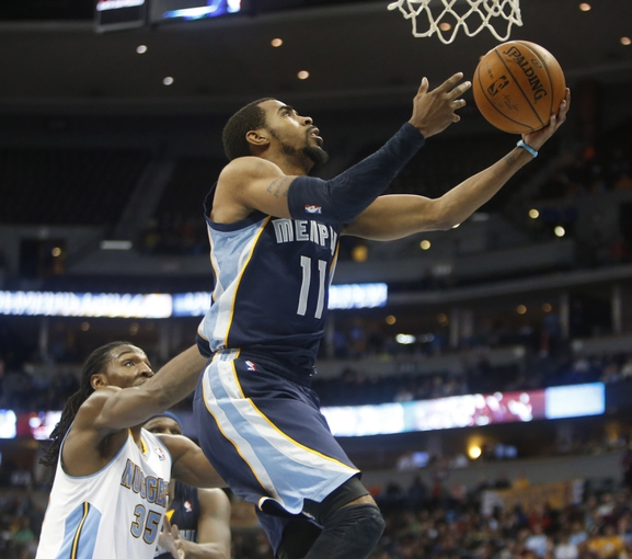 Mar 31, 2014; Denver, CO, USA; Memphis Grizzlies guard Mike Conley (11) shoots the ball during the second half against the Denver Nuggets at Pepsi Center.  The Grizzlies won 94-92.  Mandatory Credit: Chris Humphreys-USA TODAY Sports