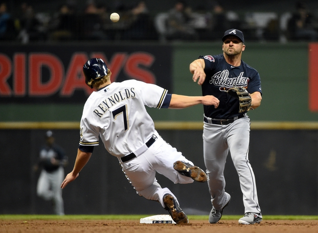 Apr 1, 2014; Milwaukee, WI, USA;  Atlanta Braves second baseman Dan Uggla (26) turns a double play after forcing out Milwaukee Brewers third baseman Mark Reynolds (7) in the second inning at Miller Park. Mandatory Credit: Benny Sieu-USA TODAY Sports