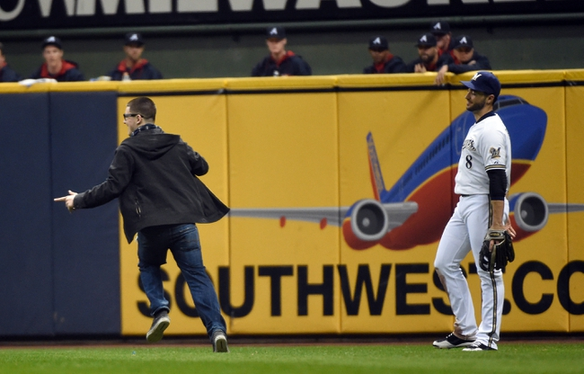 Apr 1, 2014; Milwaukee, WI, USA;  A fan runs on the field past Milwaukee Brewers right fielder Ryan Braun (8) during the game against the Atlanta Braves in the third inning at Miller Park. Mandatory Credit: Benny Sieu-USA TODAY Sports