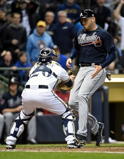 Apr 1, 2014; Milwaukee, WI, USA; Milwaukee Brewers catcher Jonathan Lucroy (20) tags out Atlanta Braves first baseman Freddie Freeman (5) trying to score in the fourth inning at Miller Park. Mandatory Credit: Benny Sieu-USA TODAY Sports