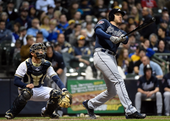 Apr 1, 2014; Milwaukee, WI, USA;  Atlanta Braves first baseman Freddie Freeman (5) hits a solo home run in the sixth inning against the Milwaukee Brewers at Miller Park. At left is Milwaukee Brewers catcher Jonathan Lucroy (20).  Mandatory Credit: Benny Sieu-USA TODAY Sports