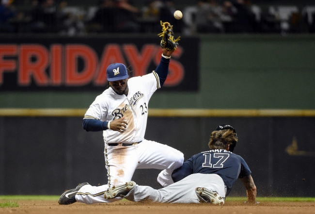 Apr 1, 2014; Milwaukee, WI, USA;  Atlanta Braves center fielder Jordan Schafer (17) steals 2nd base as the ball gets past Milwaukee Brewers second baseman Rickie Weeks (23) in the eighth inning at Miller Park. Mandatory Credit: Benny Sieu-USA TODAY Sports