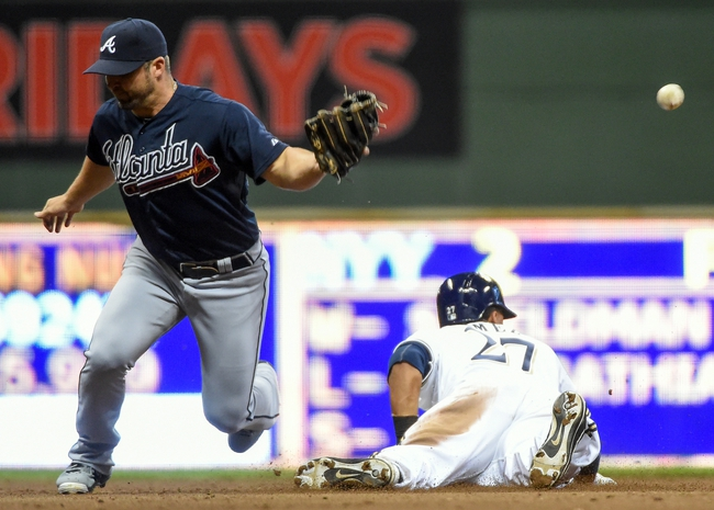 Apr 1, 2014; Milwaukee, WI, USA; Milwaukee Brewers center fielder Carlos Gomez (27) steals 2nd base as the ball gets past Atlanta Braves second baseman Dan Uggla (26) in the eighth inning at Miller Park. Mandatory Credit: Benny Sieu-USA TODAY Sports