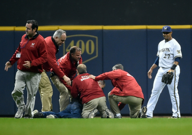 Apr 1, 2014; Milwaukee, WI, USA;  Milwaukee Brewers center fielder Carlos Gomez (27) watches as security guards remove a fan who ran on the field during the game against the Atlanta Braves in the third inning at Miller Park. Mandatory Credit: Benny Sieu-USA TODAY Sports