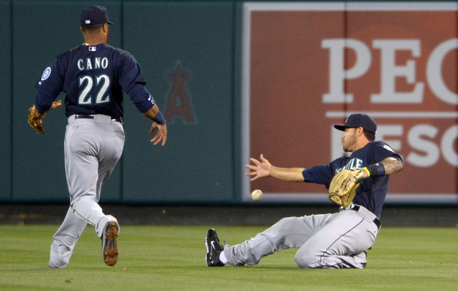 Apr 1, 2014; Anaheim, CA, USA; Seattle Mariners right fielder Stefen Romero (7) is unable to catch a fly ball by Los Angeles Angels catcher Hank Conger (not pictured) as Mariners second baseman Robinson Cano (22) watches  in the fourth inning at Angel Stadium of Anaheim. Mandatory Credit: Kirby Lee-USA TODAY Sports