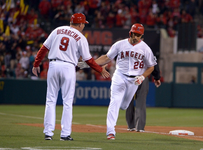 Apr 1, 2014; Anaheim, CA, USA; Los Angeles Angels designated hitter Raul Ibanez (28) is congratulated by third base coach Gary DiSarcina (9) after hitting a two-run home run in the fourth inning against the Seattle Mariners at Angel Stadium of Anaheim. Mandatory Credit: Kirby Lee-USA TODAY Sports
