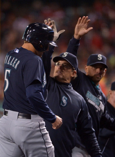 Apr 1, 2014; Anaheim, CA, USA; Seattle Mariners shortstop Brad Miller (5) is congratulated by hitting coach Howard Johnson after hitting a solo home run in the fifth inning against the Los Angeles Angels at Angel Stadium of Anaheim. Mandatory Credit: Kirby Lee-USA TODAY Sports
