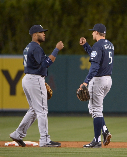 Apr 1, 2014; Anaheim, CA, USA; Seattle Mariners second baseman Robinson Cano (left) and shortstop Brad Miller celebrate at the end of the game against the Los Angeles Angels at Angel Stadium of Anaheim. The Mariners defeated the Angels 8-3. Mandatory Credit: Kirby Lee-USA TODAY Sports