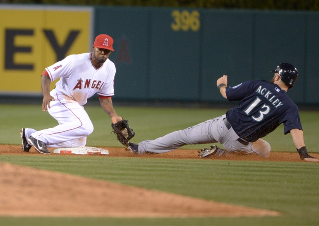 Apr 1, 2014; Anaheim, CA, USA; Seattle Mariners left fielder Dustin Ackley (13) slides beneath the tag of Los Angeles Angels second baseman Howie Kendrick (47) for a stolen base in the ninth inning at Angel Stadium of Anaheim. The Mariners defeated the Angels 8-3. Mandatory Credit: Kirby Lee-USA TODAY Sports