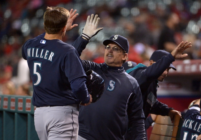 Apr 1, 2014; Anaheim, CA, USA; Seattle Mariners shortstop Brad Miller (5) is congratulated by hitting coach Howard Johnson after hitting a two run home run in the ninth inning against the Los Angeles Angels at Angel Stadium of Anaheim. Mandatory Credit: Kirby Lee-USA TODAY Sports
