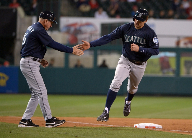 Apr 1, 2014; Anaheim, CA, USA; Seattle Mariners shortstop Brad Miller (5) is congratulated by third base coach Rich Donnelly (0) after hitting a two-run home run in the ninth inning against the Los Angeles Angels at Angel Stadium of Anaheim. The Mariners defeated the Angels 8-3. Mandatory Credit: Kirby Lee-USA TODAY Sports