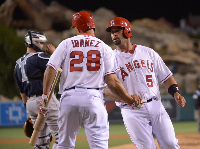 Apr 1, 2014; Anaheim, CA, USA; Los Angeles Angels first baseman Albert Pujols (5) is congratulated by designated hitter Raul Ibanez (28) after scoring in the eighth inning against the Seattle Mariners at Angel Stadium of Anaheim. The Mariners defeated the Angels 8-3. Mandatory Credit: Kirby Lee-USA TODAY Sports