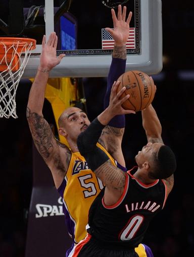 Apr 1, 2014; Los Angeles, CA, USA;  Los Angeles Lakers center Robert Sacre (50) blocks a shot by Portland Trail Blazers guard Damian Lillard (0) during the second half of the game at Staples Center. Trail Blazers won 124-112. Mandatory Credit: Jayne Kamin-Oncea-USA TODAY Sports