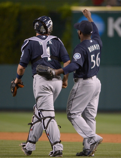 Apr 1, 2014; Anaheim, CA, USA; Seattle Mariners reliever Fernando Rodney (56) celebrates with catcher John Buck (4) at the end of the game against the Los Angeles Angels at Angel Stadium of Anaheim. The Mariners defeated the Angels 8-3. Mandatory Credit: Kirby Lee-USA TODAY Sports