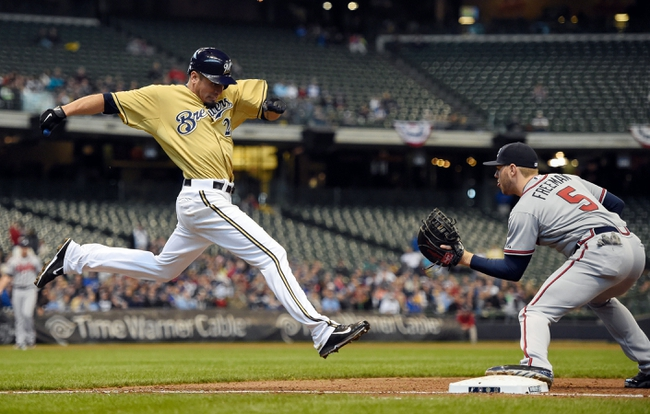 Apr 2, 2014; Milwaukee, WI, USA;  Milwaukee Brewers pitcher Matt Garza (22) is out by a step trying to beat out an infield hit as Atlanta Braves first baseman Freddie Freeman (5) gets the ball in the sixth inning at Miller Park. Mandatory Credit: Benny Sieu-USA TODAY Sports