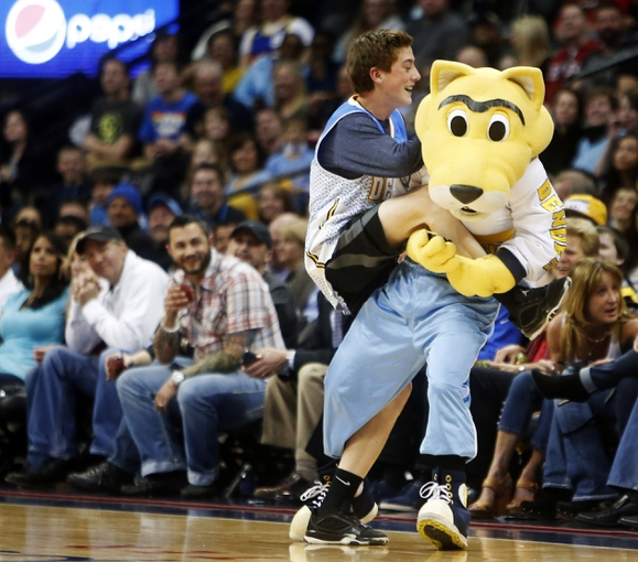 Apr 2, 2014; Denver, CO, USA; Denver Nuggets mascot Rocky wrestles a fan on the floor during the first half against the New Orleans Pelicans  at Pepsi Center. Mandatory Credit: Chris Humphreys-USA TODAY Sports