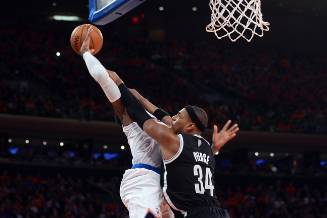 Apr 2, 2014; New York, NY, USA; Brooklyn Nets forward Paul Pierce (34) fouls New York Knicks guard Iman Shumpert (21) during the second half at Madison Square Garden. The New York Knicks won 110-81. Mandatory Credit: Joe Camporeale-USA TODAY Sports