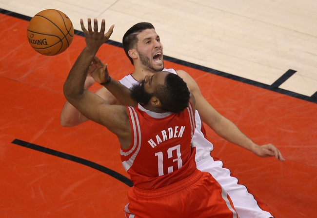 Apr 2, 2014; Toronto, Ontario, CAN; Houston Rockets guard James Harden (13) is fouled by Toronto Raptors guard Greivis Vasquez (21) at Air Canada Centre. The Raptors beat the Rockets 107-103. Mandatory Credit: Tom Szczerbowski-USA TODAY Sports