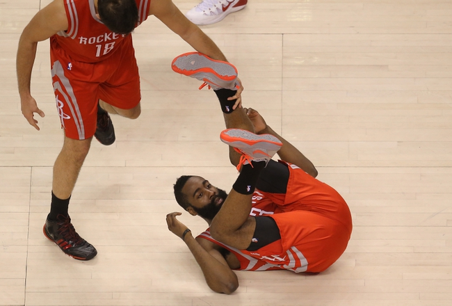 Apr 2, 2014; Toronto, Ontario, CAN; Houston Rockets guard James Harden (13) goes down to the floor while defending against the Toronto Raptors at Air Canada Centre. The Raptors beat the Rockets 107-103. Mandatory Credit: Tom Szczerbowski-USA TODAY Sports