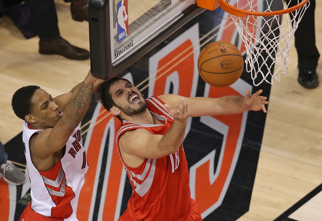 Apr 2, 2014; Toronto, Ontario, CAN; Toronto Raptors guard DeMar DeRozan (10) fouls Houston Rockets forward Omri Casspi (18) at Air Canada Centre. The Raptors beat the Rockets 107-103. Mandatory Credit: Tom Szczerbowski-USA TODAY Sports