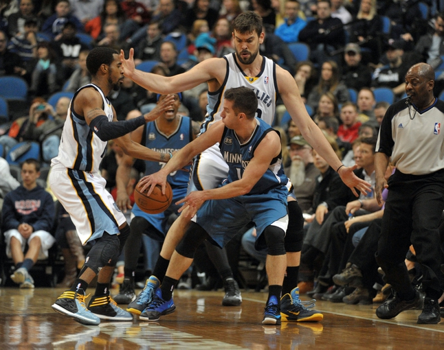Apr 2, 2014; Minneapolis, MN, USA;  Minnesota Timberwolves guard Jose Barea (11) looks to pass between Memphis Grizzlies guard Mike Conley (11) and center Marc Gasol (33) in the second quarter at Target Center. The Wolves defeated the Grizzlies 102-88.  Mandatory Credit: Marilyn Indahl-USA TODAY Sports