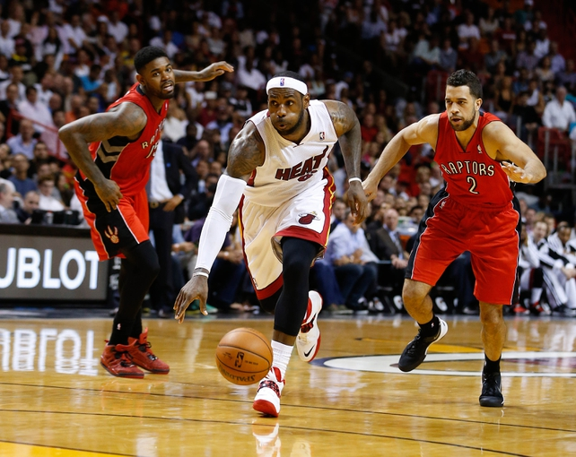 Mar 31, 2014; Miami, FL, USA;  Miami Heat forward LeBron James (6) drive to the basket between Toronto Raptors forward Amir Johnson (15) and forward Landry Fields (2) in the second half at American Airlines Arena. The Heat won 93-83. Mandatory Credit: Robert Mayer-USA TODAY Sports