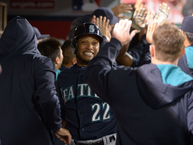 Apr 1, 2014; Anaheim, CA, USA; Seattle Mariners second baseman Robinson Cano (22) celebrates with teammates after scoring in the third inning against the Los Angeles Angels at Angel Stadium of Anaheim. Mandatory Credit: Kirby Lee-USA TODAY Sports