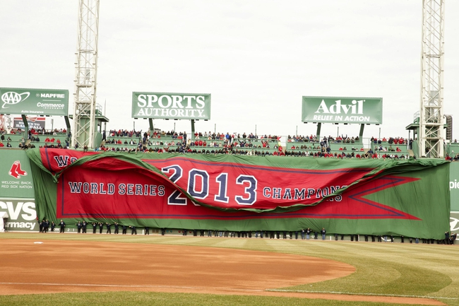 Apr 4, 2014; Boston, MA, USA; A 2013 World Series championship banner for the Boston Red Sox is unfurled on the Green Monster during pre-game ceremonies before the start of the game against the Milwaukee Brewers at Fenway Park. Mandatory Credit: David Butler II-USA TODAY Sports