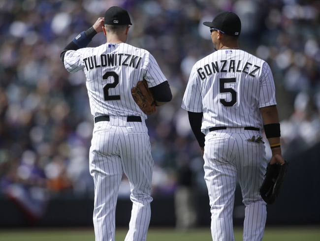 Apr 4, 2014; Denver, CO, USA; Colorado Rockies shortstop Troy Tulowitzki (2) and left fielder Carlos Gonzalez (5) during the first inning against the Arizona Diamondbacks at Coors Field. Mandatory Credit: Chris Humphreys-USA TODAY Sports