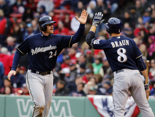 Apr 4, 2014; Boston, MA, USA; Milwaukee Brewers first baseman Lyle Overbay (24) is congratulated by teammate left fielder Ryan Braun (8) after scoring against the Boston Red Sox in the ninth inning at Fenway Park. Mandatory Credit: David Butler II-USA TODAY Sports