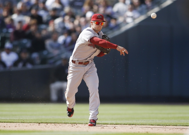 Apr 4, 2014; Denver, CO, USA; Arizona Diamondbacks shortstop Chris Owings (16) fields a ground ball during the fifth inning against the Colorado Rockies at Coors Field. Mandatory Credit: Chris Humphreys-USA TODAY Sports