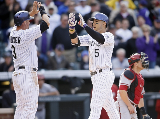 Apr 4, 2014; Denver, CO, USA; Colorado Rockies left fielder Carlos Gonzalez (5) is greeted by right fielder Michael Cuddyer (3) after hitting a home run during the sixth inning against the Arizona Diamondbacks at Coors Field. Mandatory Credit: Chris Humphreys-USA TODAY Sports