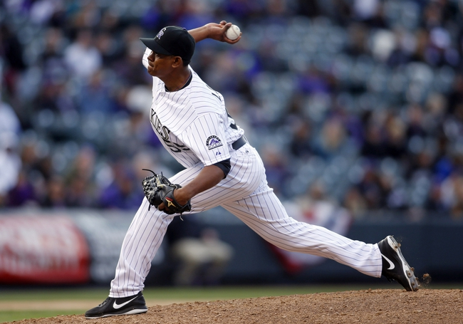 Apr 4, 2014; Denver, CO, USA; Colorado Rockies pitcher Wilton Lopez (59) delivers a pitch during the ninth inning against the Arizona Diamondbacks at Coors Field. The Rockies won 12-2. Mandatory Credit: Chris Humphreys-USA TODAY Sports