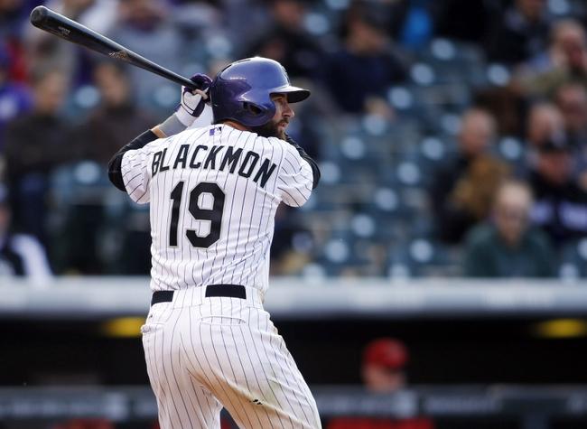 Apr 4, 2014; Denver, CO, USA; Colorado Rockies left fielder Charlie Blackmon (19) at bat during the eighth inning against the Arizona Diamondbacks at Coors Field. The Rockies won 12-2. Mandatory Credit: Chris Humphreys-USA TODAY Sports