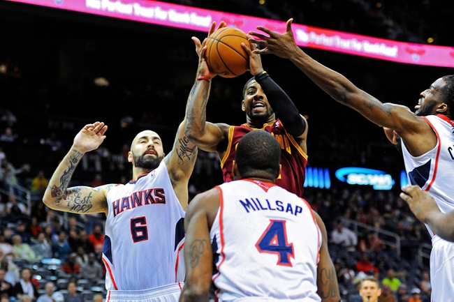 Apr 4, 2014; Atlanta, GA, USA; Cleveland Cavaliers guard Kyrie Irving (2) tries to get to the basket past Atlanta Hawks center Pero Antic (6) forward Paul Millsap (4) and forward DeMarre Carroll (5) during the first half at Philips Arena. Mandatory Credit: Dale Zanine-USA TODAY Sports