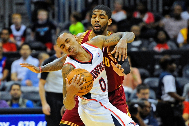 Apr 4, 2014; Atlanta, GA, USA; Atlanta Hawks guard Jeff Teague (0) is fouled by Cleveland Cavaliers guard Kyrie Irving (2) during the first half at Philips Arena. Mandatory Credit: Dale Zanine-USA TODAY Sports