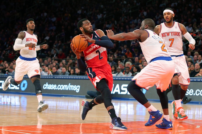 Apr 4, 2014; New York, NY, USA; Washington Wizards point guard John Wall (2) drives the lane past New York Knicks shooting guard Iman Shumpert (21) and Knicks point guard Raymond Felton (2) and small forward Carmelo Anthony (7) during the first quarter of a game at Madison Square Garden. Mandatory Credit: Brad Penner-USA TODAY Sports