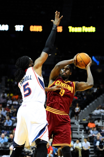 Apr 4, 2014; Atlanta, GA, USA; Atlanta Hawks  forward DeMarre Carroll (5) defends against Cleveland Cavaliers forward Luol Deng (9) during the first half at Philips Arena. Mandatory Credit: Dale Zanine-USA TODAY Sports