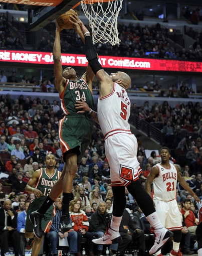 Apr 4, 2014; Chicago, IL, USA;  Milwaukee Bucks guard Giannis Antetokounmpo (34) is defended by Chicago Bulls forward Carlos Boozer (5) during the first quarter at the United Center. Mandatory Credit: David Banks-USA TODAY Sports