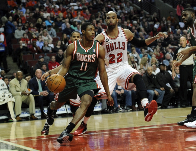 Apr 4, 2014; Chicago, IL, USA; Milwaukee Bucks guard Brandon Knight (11) is defended by Chicago Bulls forward Taj Gibson (22) during the first half at the United Center. Mandatory Credit: David Banks-USA TODAY Sports