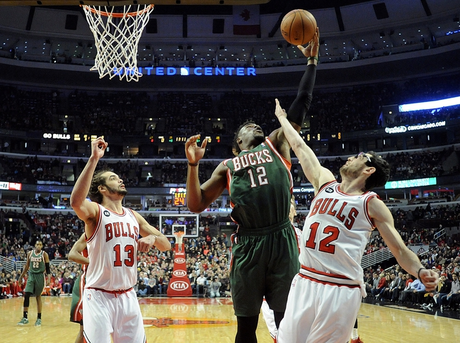 Apr 4, 2014; Chicago, IL, USA;  Milwaukee Bucks forward Jeff Adrien (12) fights for a rebound with Chicago Bulls center Joakim Noah (13) and guard Kirk Hinrich (12)  during the first quarter at the United Center. Mandatory Credit: David Banks-USA TODAY Sports