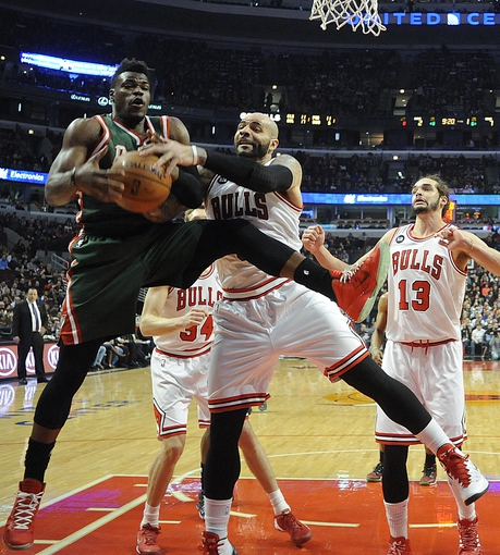 Apr 4, 2014; Chicago, IL, USA;  Milwaukee Bucks forward Jeff Adrien (12) and Chicago Bulls forward Carlos Boozer (5) fight for the ball during the first quarter at the United Center. Mandatory Credit: David Banks-USA TODAY Sports