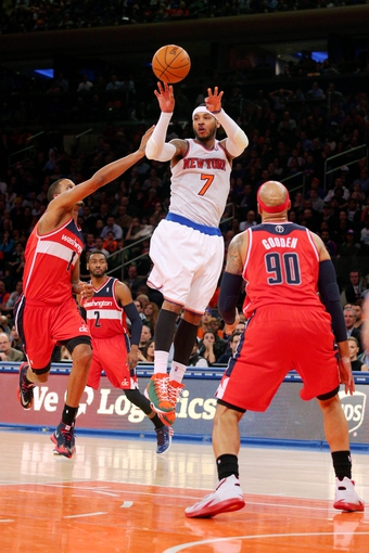 Apr 4, 2014; New York, NY, USA; New York Knicks small forward Carmelo Anthony (7) passes the ball while defended by Washington Wizards small forward Trevor Ariza (1) and Wizards point guard John Wall (2) and power forward Drew Gooden (90) during the fourth quarter of a game at Madison Square Garden. The Wizards defeated the Knicks 90-89. Mandatory Credit: Brad Penner-USA TODAY Sports