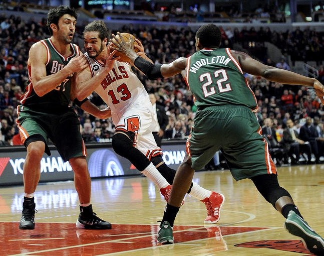 Apr 4, 2014; Chicago, IL, USA;  Chicago Bulls center Joakim Noah (13) is guarded by Milwaukee Bucks center Zaza Pachulia (27) and forward Khris Middleton (22) during the second half at the United Center. The Chicago Bulls defeated the Milwaukee Bucks 102-90. Mandatory Credit: David Banks-USA TODAY Sports