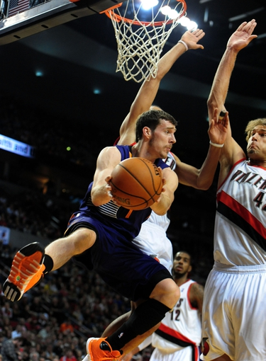 Apr 4, 2014; Portland, OR, USA; Phoenix Suns guard Goran Dragic (1) looks to pass the ball as Portland Trail Blazers center Robin Lopez (42) defends during the first quarter of the game at Moda Center. Mandatory Credit: Steve Dykes-USA TODAY Sports
