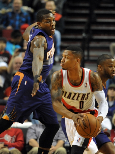 Apr 4, 2014; Portland, OR, USA; Phoenix Suns guard Eric Bledsoe (2) defends against Portland Trail Blazers guard Damian Lillard (0) during the first quarter of the game at Moda Center. Mandatory Credit: Steve Dykes-USA TODAY Sports