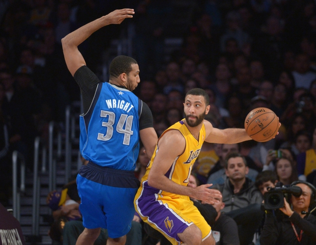 Apr 4, 2014; Los Angeles, CA, USA; Los Angeles Lakers guard Kendall Marshall (12) is defended by Dallas Mavericks forward Brendan Wright (34) at Staples Center. Mandatory Credit: Kirby Lee-USA TODAY Sports
