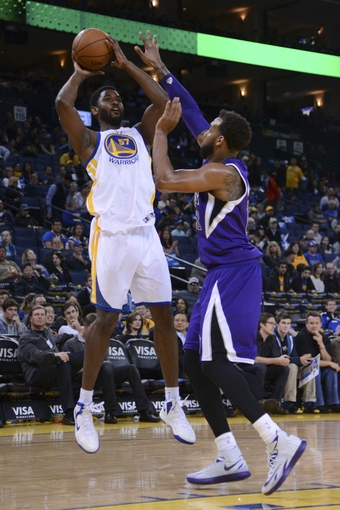 April 4, 2014; Oakland, CA, USA; Golden State Warriors forward Hilton Armstrong (57) shoots against Sacramento Kings forward Derrick Williams (13, right) during the fourth quarter at Oracle Arena. The Warriors defeated the Kings 102-69. Mandatory Credit: Kyle Terada-USA TODAY Sports